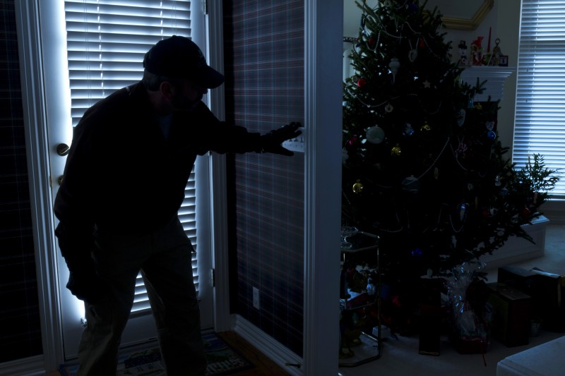 This photo illustrates a burglary or thief breaking into a home at night through a back door during the Christmas Holiday Season. View from inside the residence.